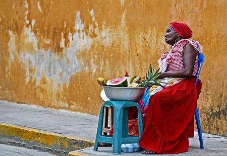comida colombiana: CARTAGENA DE INDIAS, COLOMBIA - 21 de diciembre: Sin determinar mujer palenquera vender fruts en Cartagena de Indias el 21 de diciembre de 2010, Palenqueras son un grupo �nico descendat �tnicos africanos se encuentran en la regi�n norte de Am�rica del Sur