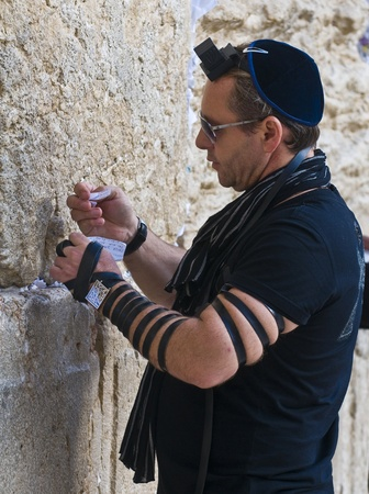 JERUSALEM - NOVEMBER 03 2011 : A jewish man lay tefillin in The western wall an Important Jewish religious site located in the Old City of Jerusalem , Israel