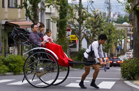 KYOTO , JAPAN - OCT 24 : Japanese family on a trditional rickshaw being pulled by a man on October 24 2009 in Kyoto , Japan