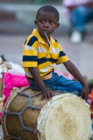 CARTAGENA , COLOMBIA - DEC 22 : Local child sitting on a drum while preparation for the celebration , held in the Unesco world heritage city of Cartagena , Colombia on December 22 2010 Editorial