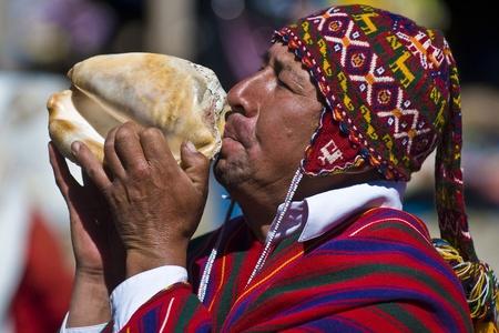 quechua: CHINCHERO , PERU - MAY 29 2011 : An unidentified Peruvian man with traditional clothes blowing a shell on May 27 2011 in Chinchero Peru , shell blowing is traditional in Peru