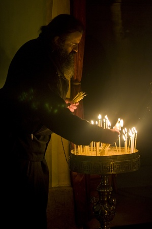 JERUSALEM - DECEMBER 18 2011 - A pilgrim priest prays by a candelelight in the church of the holy sepulcher in Jrusalem Israel