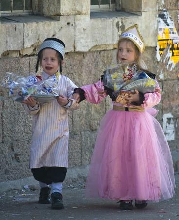 chassidim: GERUSALEMME - MARS 09: Ultra bambini ortodossi in possesso di Mishloach Manot durante Purim in Gerusalemme, Mea Shearim su Marte 09 2012, Mishloach Manot � doni alimentari tradizionali somministrate durante il Purim