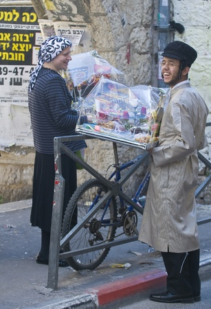 hasidim: JERUSALEM - MARS 09 : Ultra Orthodox couple holding Mishloach Manot during Purim in Mea Shearim Jerusalem on Mars 09 2012 , Mishloach Manot is traditional food gifts given during Purim
