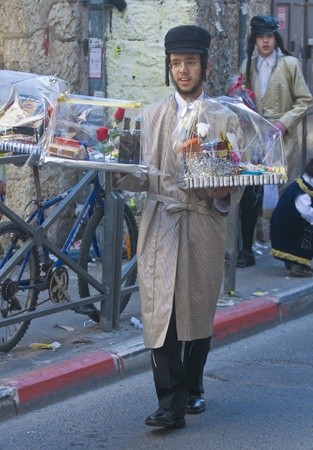 shearim: JERUSALEM - MARS 09 : Ultra Orthodox man holding Mishloach Manot during Purim in Mea Shearim Jerusalem on Mars 09 2012 , Mishloach Manot is traditional food gifts given during Purim Editorial