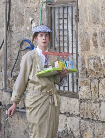 chassidim: GERUSALEMME - MARS 09: ultra ortodossi uomo azienda Mishloach Manot durante Purim a Mea Shearim a Gerusalemme su Marte 09 2012, Mishloach Manot � doni alimentari tradizionali fornite durante Purim