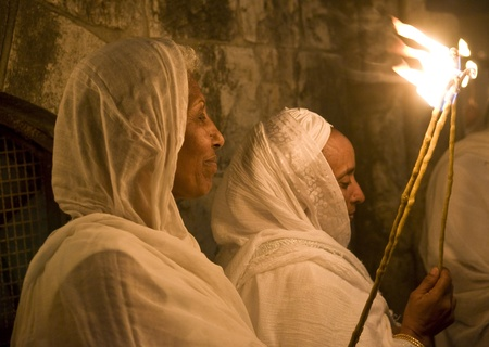 worshipers: JERUSALEM - APRIL 14 : Ethiopian Orthodox worshipers hold candles during the Holy fire ceremony at the Ethiopian section of the Holy Sepulcher in Jerusalm Israel on April 14 2012