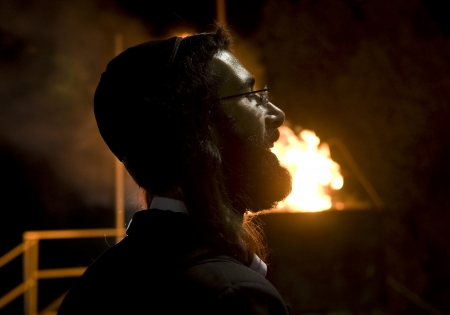exprassion: MERON , ISRAEL - MAY 10 : Jewish man near a bonfire during Lag Baomer in Bar Yochai tomb in Meron , Israel on May 10 2012 , Lag Baomer is a Jewish holiday in wich it is customary to light bonfire Editorial