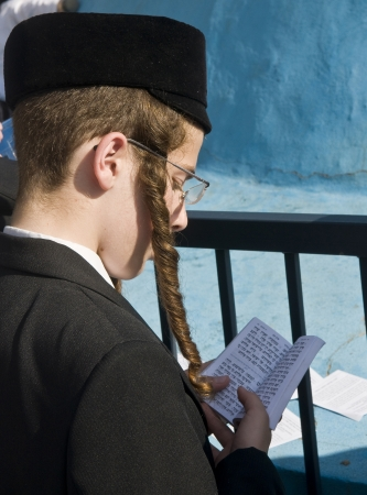 exprassion: MERON , ISRAEL - MAY 10 : Jewish boy prays during Lag Baomer in Bar Yochai tomb in Meron , Israel on May 10 2012 , Lag Baomer is a Jewish holiday in wich it is customary to light bonfire Editorial