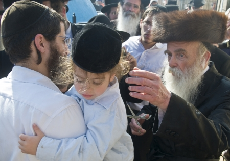 MERON , ISRAEL - MAY 10 : Rabbi cuts childs hair in a Halake ceremony in Bar Yochai tomb in Meron , Israel on May 10 2012 , Halake is first haircut ceremony celebrated in Lag Baomer