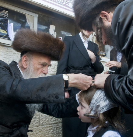 exprassion: MERON , ISRAEL - MAY 10 : Rabbi cuts childs hair in a Halake ceremony in Bar Yochai tomb in Meron , Israel on May 10 2012 , Halake is first haircut ceremony celebrated in Lag Baomer  Editorial