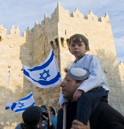 JERUSALEM - MAY 20 2012 : Right wing Israeli boy with his father on Jerusalem day in front of Damascus gate before marching throuh the Arab quarter of Jerusalem old city on May 20 2012 , Jerusalem day marks the anniversary of Israel capturing the eastern