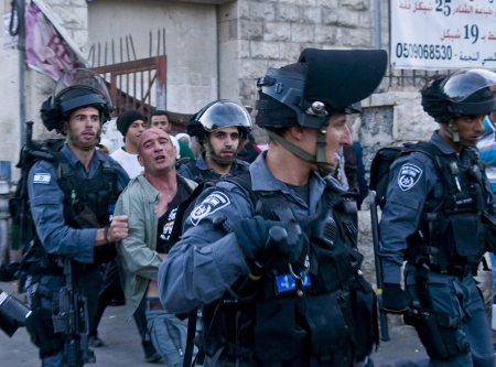 JERUSALEM - MAY 20 2012 : Israeli border policemen detain a Palestinian demonstrating against tens of thousand Israeli right wingers commemorating Jerusalem day with a march to Jerusalem old city on May 20 2012 , Jerusalem day marks the anniversary of Isr Editorial