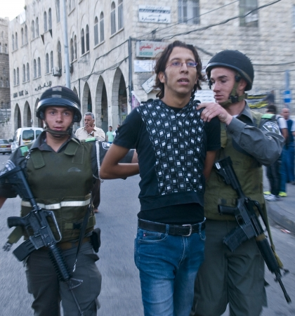 JERUSALEM - MAY 20 2012 : Israeli border policemen detain a Palestinian demonstrating against tens of thousand Israeli right wingers commemorating Jerusalem day with a march to Jerusalem old city on May 20 2012 , Jerusalem day marks the anniversary of Isr