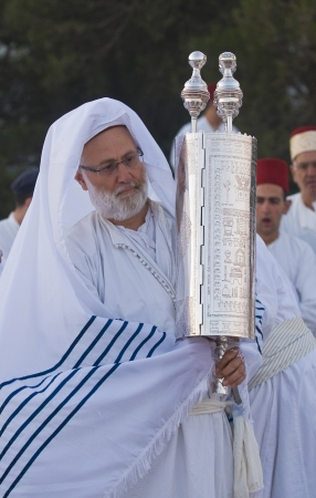 NABLUS, WEST BANK - JUNE 24 : A priest of the ancient Samaritan community holds up a Torah scroll during the holy day of Shavuot in Mount Gerizim on June 24 2012, Shavuot is an holyday commemoretas the anniversary of the day god have given the Torah to th Stock Photo - 14174612