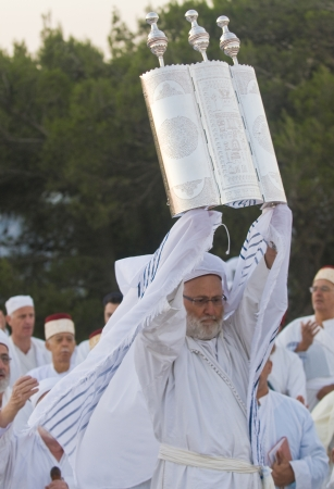 NABLUS, WEST BANK - JUNE 24 : A priest of the ancient Samaritan community holds up a Torah scroll during the holy day of Shavuot in Mount Gerizim on June 24 2012, Shavuot is an holyday commemoretas the anniversary of the day god have given the Torah to th Stock Photo - 14174624