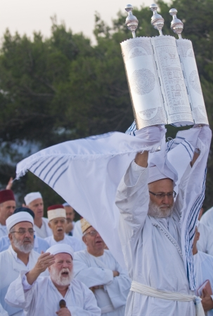 NABLUS, WEST BANK - JUNE 24 : A priest of the ancient Samaritan community holds up a Torah scroll during the holy day of Shavuot in Mount Gerizim on June 24 2012, Shavuot is an holyday commemoretas the anniversary of the day god have given the Torah to th Stock Photo - 14174630