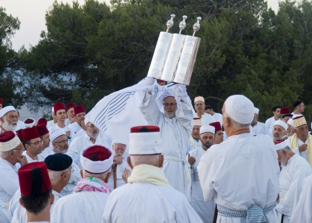 NABLUS, WEST BANK - JUNE 24 : A priest of the ancient Samaritan community holds up a Torah scroll during the holy day of Shavuot in Mount Gerizim on June 24 2012, Shavuot is an holyday commemoretas the anniversary of the day god have given the Torah to th