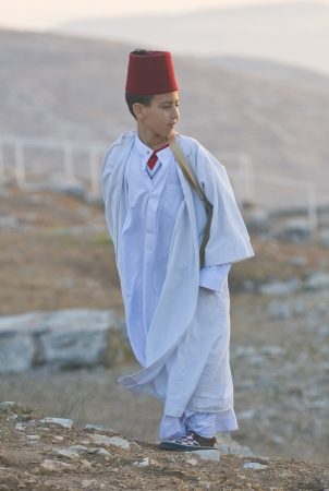nablus: NABLUS, WEST BANK - JUNE 24 : Young Member of the ancient Samaritan community during the holy day of Shavuot in Mount Gerizim on June 24 2012, Shavuot is an holyday commemoretas the anniversary of the day god have given the Torah to the Israelites Editorial