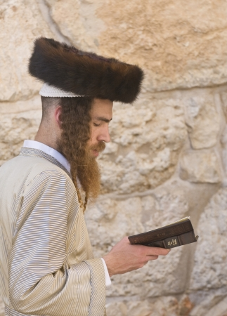 JERUSALEM - APRIL 08 : Orthodox jewish men prays in The western wall during Passover on April 08 2012 , The Western wall is important Jewish religious site located in the Old City of Jerusalem  Stock Photo - 14340364