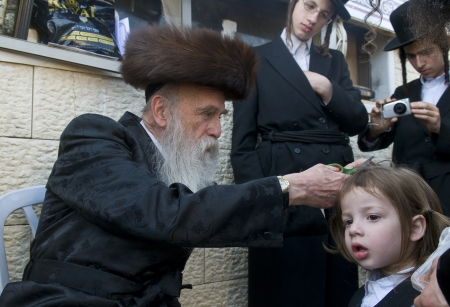 MERON , ISRAEL - MAY 10 : Rabbi cuts child's hair in a Halake ceremony in Bar Yochai tomb in Meron , Israel on May 10 2012 , Halake is first haircut ceremony celebrated in Lag Ba'omer
