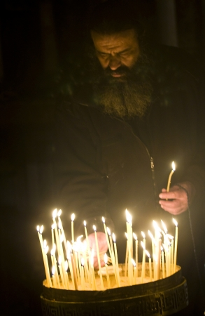 sepulcher: JERUSALEM - DECEMBER 18 2011 - A pilgrim priest prays by a candelelight in the church of the holy sepulcher in Jrusalem Israel