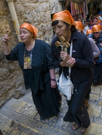 dolorosa: JERUSALEM - APRIL 13 : Christian pilgrims carry across along the Via Dolorosa in Jerusalem on April 13 2012 commemorating the path Jesus carried his cross on the day of his crucifixion