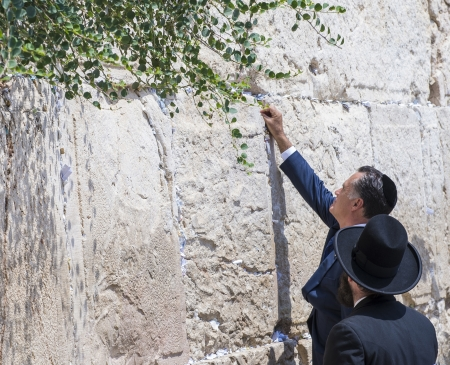 JEUSALEM - JULY 29 :  US Republican presidential candidate Mitt Romney places a mesage written on paper in the stones of the Western wall during his visit to Jerusalem Israel on July 29 2012