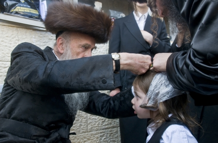 MERON , ISRAEL - MAY 10 : Rabbi cuts childs hair in a Halake ceremony in Bar Yochai tomb in Meron , Israel on May 10 2012 , Halake is first haircut ceremony celebrated in Lag Baomer  Editorial