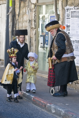 hasidim: JERUSALEM - MARS 09 : Ultra Orthodox man give presents to a children during Purim in Mea Shearim Jerusalem on Mars 09 2012 , Giving presents to children is a tradition of Purim Editorial