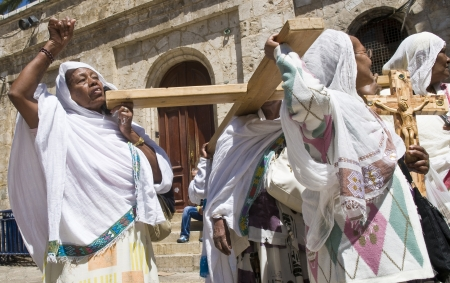 spirtual: JERUSALEM - APRIL 13 : Ethiopian Christian pilgrims carry across along the Via Dolorosa in Jerusalem on April 13 2012 commemorating the path Jesus carried his cross on the day of his crucifixion