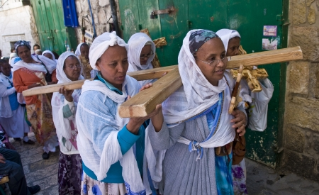 cros: JERUSALEM - APRIL 13 : Ethiopian Christian pilgrims carry across along the Via Dolorosa in Jerusalem on April 13 2012 commemorating the path Jesus carried his cross on the day of his crucifixion