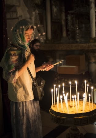 JERUSALEM - JULY 29 2012 - A pilgrim prays by candelelight in the church of the holy sepulcher in Jerusalem Israel