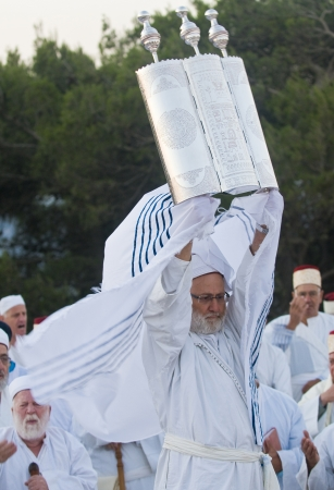 shavuot: NABLUS, WEST BANK - JUNE 24 : A priest of the ancient Samaritan community holds up a Torah scroll during the holy day of Shavuot in Mount Gerizim on June 24 2012, Shavuot is an holyday commemoretas the anniversary of the day god have given the Torah to th