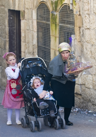 JERUSALEM - MARS 09 : Ultra Orthodox family during Purim in Mea Shearim Jerusalem on Mars 09 2012 , Purim is a Jewish holiday celebrates the salvation of the jews from jenocide in ancient Persia Stock Photo - 14904622