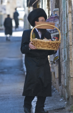 haredi: JERUSALEM - MARS 09 : Ultra Orthodox man holding Mishloach Manot during Purim in Mea Shearim Jerusalem on Mars 09 2012 , Mishloach Manot is traditional food gifts given during Purim Editorial