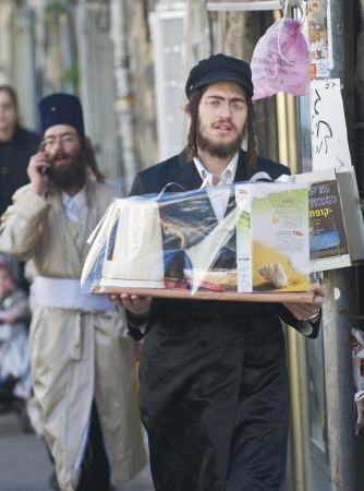hasidic: JERUSALEM - MARS 09 : Ultra Orthodox man holding Mishloach Manot during Purim in Mea Shearim Jerusalem on Mars 09 2012 , Mishloach Manot is traditional food gifts given during Purim Editorial
