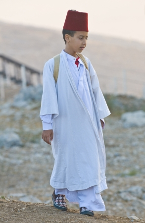 samaritans: NABLUS, WEST BANK - JUNE 24 : Young Member of the ancient Samaritan community during the holy day of Shavuot in Mount Gerizim on June 24 2012, Shavuot is an holyday commemoretas the anniversary of the day god have given the Torah to the Israelites Editorial