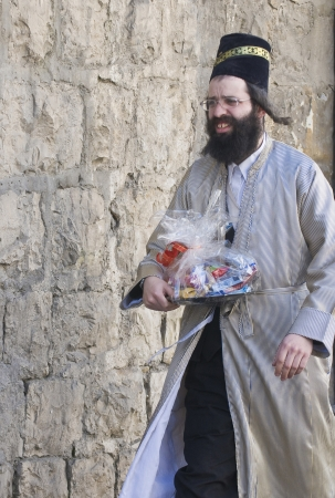 mea shearim: JERUSALEM - MARS 09 : Ultra Orthodox man holding Mishloach Manot during Purim in Mea Shearim Jerusalem on Mars 09 2012 , Mishloach Manot is traditional food gifts given during Purim Editorial