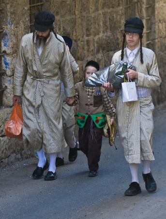 mea: JERUSALEM - MARS 09 : Ultra Orthodox family during Purim in Mea Shearim Jerusalem on Mars 09 2012 , Purim is a Jewish holiday celebrates the salvation of the jews from jenocide in ancient Persia  Editorial