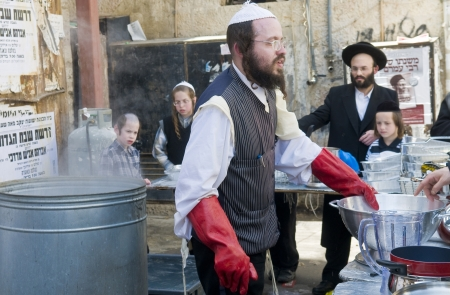 hasidim: JERUSALEM - APRIL 05 : An Ultra Orthodox man is preparing to the Jewish holiday of Passover by purifacation of the dishes in Jerusalem Israel on April 05 2012 Editorial