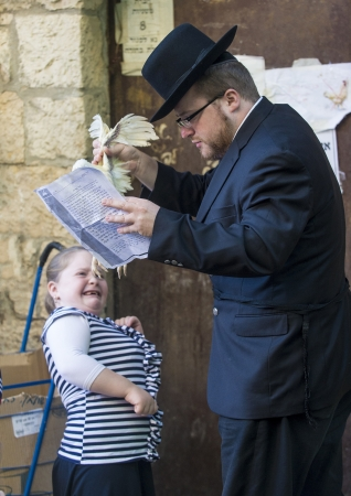 exprassion: JERUSALEM - SEP 25 : An ultra Orthodox Jewish man waves a chicken over his childs heads during the Kaparot ceremony held in Jerusalem Israel in September 25 2012