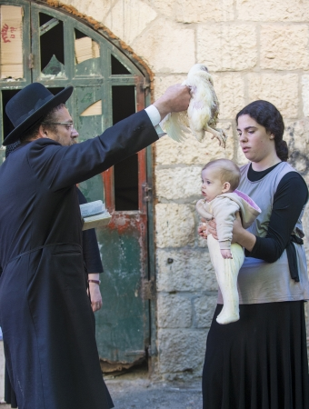 JERUSALEM - SEP 25 : An ultra Orthodox Jewish man waves a chicken over his childs heads during the Kaparot ceremony held in Jerusalem Israel in September 25 2012