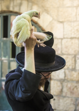 exprassion: JERUSALEM - SEP 25 : An ultra Orthodox Jewish man waves a chicken over his head during the Kaparot ceremony held in Jerusalem Israel in September 25 2012