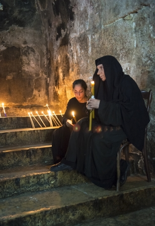 nuns: JERUSALEM - AUGUST 25 : Unidentified nuns prays in the Tomb of Mary in Gethsemane during the feast of the Assumption of the Virgin Mary on August 25 2012 in old Jerusalem Israel
