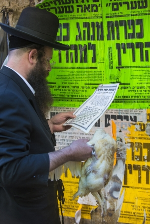 atonement: JERUSALEM - SEP 25 : An ultra Orthodox Jewish man prays with a chicken during the Kaparot ceremony held in Jerusalem Israel in September 25 2012
