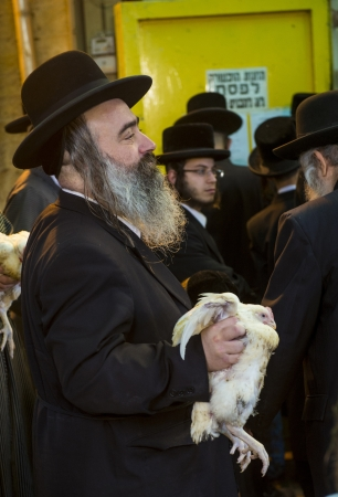 exprassion: JERUSALEM - SEP 25 : An ultra Orthodox Jewish man holds a chicken during the Kaparot ceremony held in Jerusalem Israel in September 25 2012
