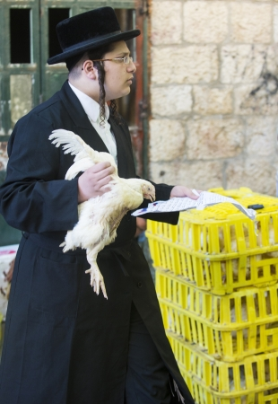 kippa: JERUSALEM - SEP 25 : An ultra Orthodox Jewish man prays with a chicken during the Kaparot ceremony held in Jerusalem Israel in September 25 2012