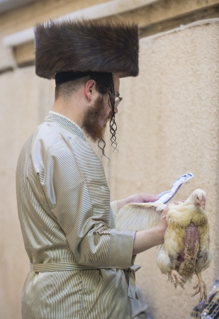 exprassion: JERUSALEM - SEP 25 : An ultra Orthodox Jewish man prays with a chicken during the Kaparot ceremony held in Jerusalem Israel in September 25 2012