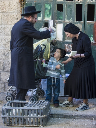 JERUSALEM - SEP 25 : An ultra Orthodox Jewish man waves a chicken over his child's heads during the Kaparot ceremony held in Jerusalem Israel in September 25 2012